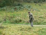 Conservation Volunteer raking off the cut vegetation