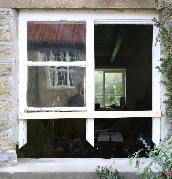By cutting out the decayed areas of timber, and carefully removing the cylinder glass (supporting the frame with a batten), new timber can be spliced in and the glass reinstated.