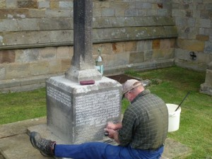 Re-engraving the inscription on the Lythe War Memorial - copyright NYMNPA