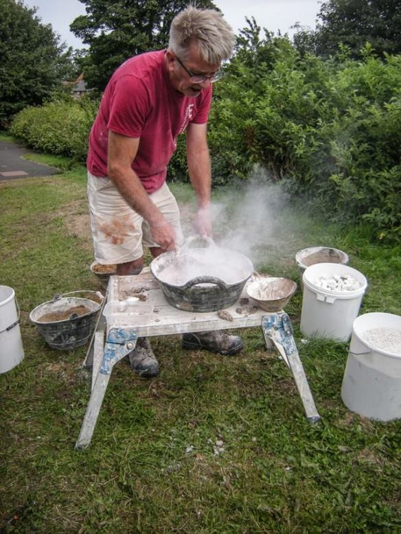 Nigel Copsey demonstrating the reaction from mixing hot lime mortar. Copyright NYMNPA,